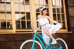 Oddolny strzał ładna dziewczyna na turkusowym rowerze blisko kawiarni fotografia royalty free