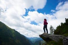 Oddolny strzał młoda żeńska turystyczna pozycja na górze rockowego podziwia niebieskiego nieba zadziwiającej scenerii w Rumunia i obrazy stock
