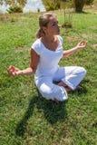 Oddychania 20s blond dziewczyna medytuje w zielonych surrondings Obrazy Stock