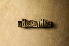 ODEFINIERAT - närbild av det typsatta ordet för grungy tappning på metallbakgrunden stock illustrationer