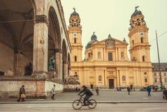Odeonsplatz quadrato occupato con i ciclisti ed i pedoni vicino alle strutture storiche Fotografie Stock