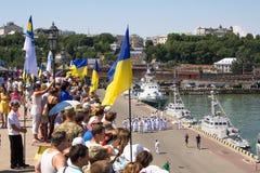 Odesa,乌克兰- 2016年7月03日:在庆祝乌克兰海军天期间,有旗子的人们在傲德萨海口船坞  库存照片