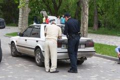 Odesa, de Oekraïne - Mei 15, 2016: Oekraïense politieman en bestuurders het vullen documenten Stock Foto