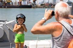 Odesa Ukraina - Juli 03, 2016: Farfar som fotograferar en pojke i militär hjälm på den nya krigsskeppet 'Akerman Royaltyfri Bild