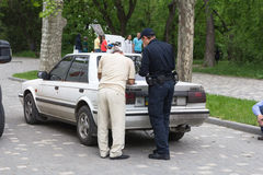 Odesa, Ukraine - May 15, 2016: Ukrainian police officer and driver filling documents. After accident Stock Photo