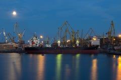 ODESSA, de OEKRAÏNE - Augustus 2016: verscheep het leegmaken bij haventerminal onder volle maan in avond met kranencontainers en Royalty-vrije Stock Afbeeldingen