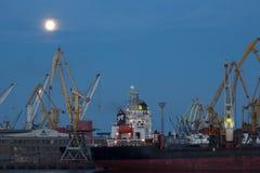 ODESSA, de OEKRAÏNE - Augustus 2016: verscheep het leegmaken bij haventerminal onder volle maan in avond met kranencontainers en stock afbeeldingen