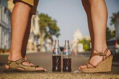 ODESSA, UCRÂNIA - 15 DE OUTUBRO DE 2014: Feche acima dos pés da mulher que estão na frente do verão do homem fora Pepsi no vidro Fotografia de Stock Royalty Free