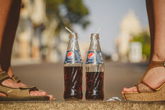 ODESSA, UCRÂNIA - 15 DE OUTUBRO DE 2014: Feche acima dos pés da mulher que estão na frente do verão do homem fora Pepsi no vidro Fotos de Stock