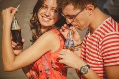 ODESSA, UCRÂNIA - 15 DE OUTUBRO DE 2014: Feche acima dos pares de sorriso novos bonitos no amor, abraçando o frio fora bebendo Fotos de Stock Royalty Free