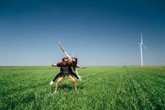 ODESSA, UCRÂNIA - PODEM, 20 2015: O moderno que novo bonito o par está caçoando no meio do campo verde com uma prancha, menina é  fotos de stock royalty free