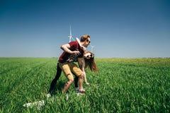 ODESSA, UCRAINA - PUÒ, 20 2015: I giovani pantaloni a vita bassa che svegli la coppia sta scherzando in mezzo al campo verde con  immagine stock libera da diritti