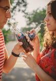 ODESSA, UCRANIA - 15 DE OCTUBRE DE 2014: Ciérrese para arriba de los pares jovenes felices al aire libre que beben Pepsi frío de  Imagen de archivo