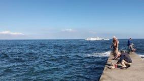 Odessa, Ucrania - 12 de septiembre de 2018: Vista lateral de pescadores en el embarcadero del mar almacen de metraje de vídeo