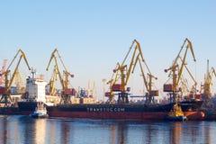 Odessa - Ukraina: januari 2, 2017: Skurkroll-elevator en marin- skyttel eskorteras av ett bogserbåtfartyg ut ur hamnen Porten av  arkivfoto