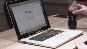 Odessa Ukraina, Listopad, - 11, 2018 Mężczyzna inaccurately nalewał koli na macbook laptopie Dolewanie ciecz w laptopu komputer o zdjęcie wideo