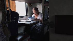 ODESSA UKRAINA, SEP, - 10, 2018: Starszej kobiety czytelnicza gazeta na pociągu zbiory wideo