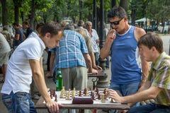 ODESSA UKRAINA, SIERPIEŃ, - 14, 2015: Młodzi człowiecy bawić się szachy w parku Odessa, Ukraina obrazy stock