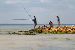 Odessa, Ukraine - August 31, 2013: Family life on the wild beach. Father is engaged in fishing. Stock Photos