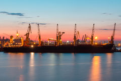 ODESSA, UKRAINE - August 2016: ship unloading at port terminal under full moon in evening with cranes containers and Royalty Free Stock Image