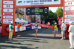 Woman winning race and coming first to finish. ODESSA, UKRAINE - CIRCA AUG 2018: Happy woman winning race and coming first to finish red ribbon royalty free stock photos