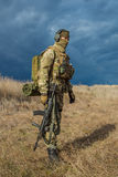 Odessa, Ukraine - December 02, 2015: Soldier with a gun in the medical field. Soldiers in a medical with a gun standing in a field in the rays of the setting sun Royalty Free Stock Photography