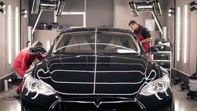 ODESSA, UKRAINE - DECEMBER 06, 2017 Two professional workers polish new black Tesla car from both sides. Making it look. Extra-shiny stock video