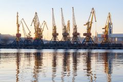 Odessa, Ukraine - Januadry 02, 2017: Container cranes in cargo port terminal, cargo cranes reflected in water. Sunset royalty free stock image