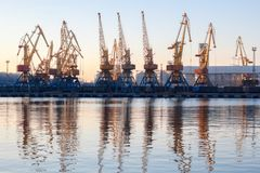 Odessa, Ukraine - Januadry 02, 2017: Container cranes in cargo port terminal, cargo cranes reflected in water. Sunset royalty free stock photo