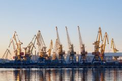 Odessa, Ukraine - Januadry 02, 2017: Container cranes in cargo port terminal, cargo cranes reflected in water. Sunset stock photo