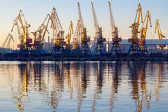 Odessa, Ukraine - Januadry 02, 2017: Container cranes in cargo port terminal, cargo cranes reflected in water. Sunset stock photos