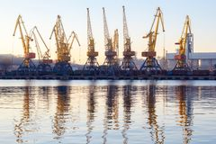 Odessa, Ukraine - Januadry 02, 2017: Container cranes in cargo port terminal, cargo cranes reflected in water. Sunset stock images