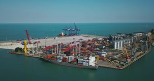 Sea cargo port with big warehouse. Odessa, Ukraine - 24 July 2017: Sea cargo port with a large warehouse with many multicolored containers. There are big cranes stock video
