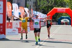 Excited male runner crossing the finshline of a marathon. ODESSA, UKRAINE - 25 JUN 2017: Excited marathon runners crossing the finshline. Marathon winners at Royalty Free Stock Images