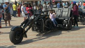 ODESSA, UKRAINE - JUNE 11 2016: Bike Cars and Rock n Roll retro festival. Two childs siting on huge custom build motorcycle. stock footage