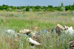 Odessa, Ukraine - June 08, 2019: Garbage scattered in the field near the forest. Pollution of nature stock photography