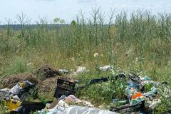 Odessa, Ukraine - June 08, 2019: Garbage scattered in the field near the forest. Pollution of nature.  stock photo
