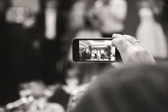 ODESSA, UKRAINE - 30. MAI 2015: Frauenhandaufnahmevideo mit Smartphone von Leuten in dem Stadium an der Abschlussfeier Lizenzfreie Stockfotos