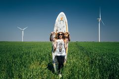 ODESSA, UKRAINE - MAY, 20 2015: Cute young hipster couple is kidding in the middle of green field with a surfboard, happy outdoor stock photos