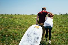 ODESSA, UKRAINE - MAY, 20 2015: Cute young hipster couple of surfers with a surfboard is on the way to the beach. Back view royalty free stock image