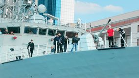 Odessa, Ukraine - September 2019: Civilian young men inspect the awesome cannon of the gun of a warship of NATO