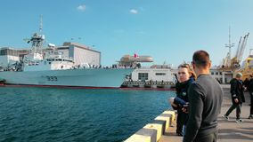 Odessa, Ukraine - September 2019: Civilians on the pier view and photograph the NATO fleet. Several warships moored in
