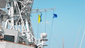 Odessa, Ukraine - September 2019: Flags of NATO and Ukraine aboard a warship. People look through binoculars and examine