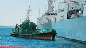 Odessa, Ukraine - September 2019: Green tugboat is working with a nato warship