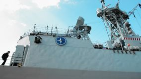 Odessa, Ukraine - September 2019: NATO military emblem aboard a warship. Several sailors go inside the ship