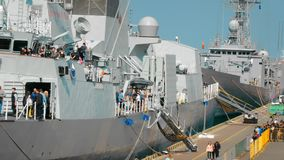 Odessa, Ukraine - September 2019: Several NATO warships are moored in the port. Civilians are walking nearby