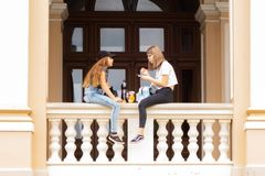 Odessa. Ukraine.2018.07.26. Two girls are sitting on the parapet of the Opera House and talking lively. royalty free stock photo
