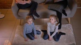 Odgórny strzał małe caucasian dziewczyny ogląda film attentively i opowiada z each inny w cosy domowej atmosferze zbiory