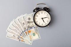Odgórny widok Czarny metalu budzik na stosie dolarów banknoty Mieszkanie nieatutowy robi pieniądze czas Budzik i dolary zdjęcia stock