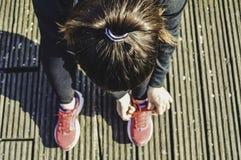Odgórny widok młoda sprawności fizycznej kobieta wiąże shoelaces, przygotowywa iść biegać zdjęcie royalty free